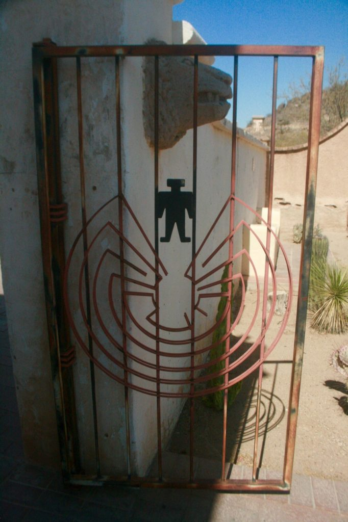 Tonto O'odham man in the maze symbol on a get next to solar lion head at San Xavier Mission
