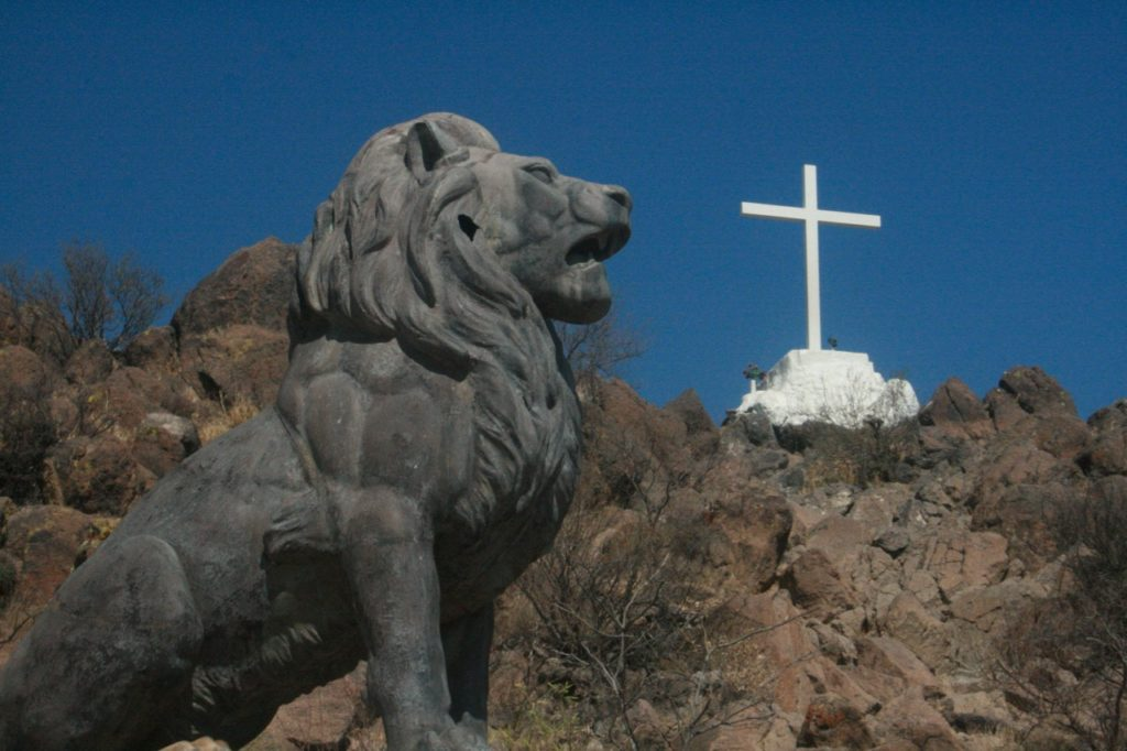 Bronze lion solar symbol below cross solar symbol next to San Xavier Mission