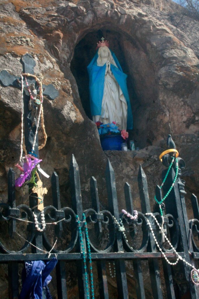 offerings at shrine with madonna on the cross mound by San Xavier mission