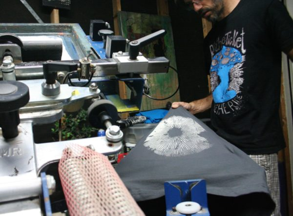 Scott Myst in the studio screen printing the mushroom spore print t shirt